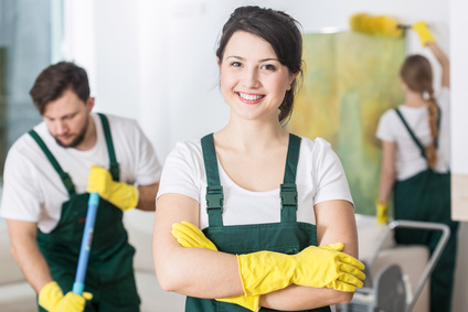 Smiling cleaning lady in uniform and yellow rubber gloves