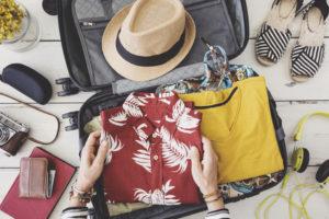 Woman hand preparing summer luggage