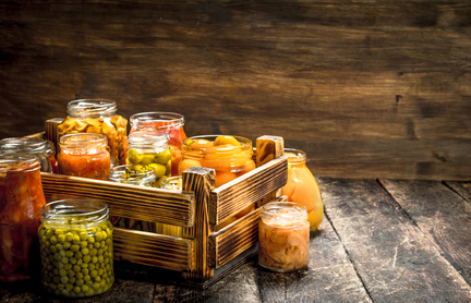Preserves mushrooms and vegetables in a box. On a wooden background.