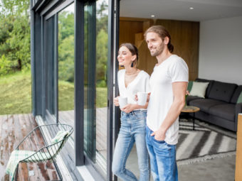 Young couple dressed in white shirts and jeans standing together outdoors on the terrace of the modern house