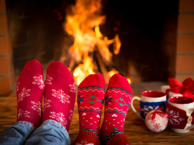 Couple relaxing at home. Feet in Christmas socks near fireplace. Winter holiday concept